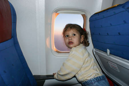 a child looks out the window on an airplane