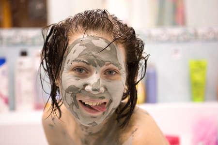 Beautiful girl with mud on his face. Cosmetic mask. Beauty face. 版權商用圖片