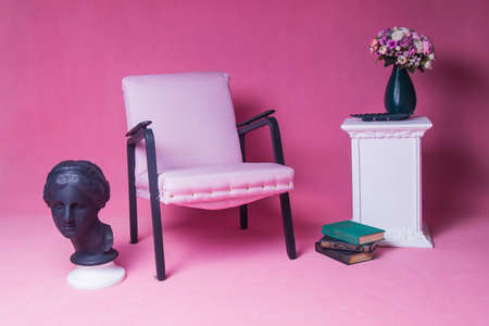 White upholstered chair on a pink background