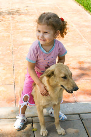 A child lovingly hugs his beloved red dog 版權商用圖片