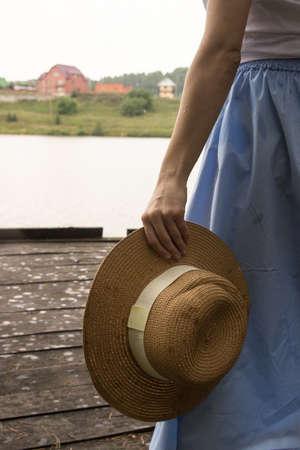women's straw hat, hold in hand in summer.