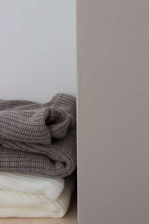 A stack of wool sweaters on the shelf. Grey and white sweater. Warm and cozy. Knitted clothing. winter clothing. 版權商用圖片