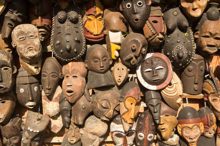 Traditional african masks hanging for sell in a market stall.