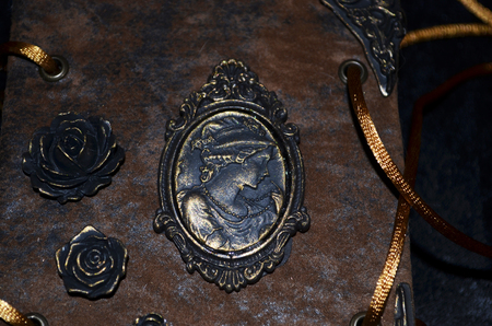 Closeup of a cameo and roses on an old-looking handmade notebook