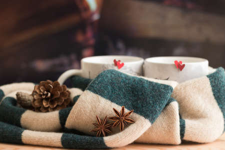 Love Mood and stay warm together - Romantic Creative Still life Composition. Close-up Warm Green Beige Scarf Tied Two Mugs with Red Hearts. Spicy Drink. Background is firewood in fireplace.