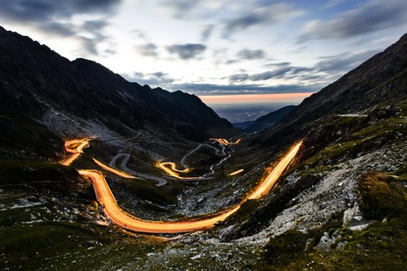 balea: Night view of picturesque Transfagarasan Highway serpentine panorama in Romania Carpathians shined with car light trails taken from high viewpoint at Balea lake Stock Photo