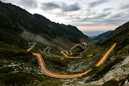 Vista nocturna del pintoresco panorama serpenteante de la autopista Transfagarasan en los Cárpatos de Rumania brillaron con estelas de luz de coche tomadas desde el mirador alto en el lago Balea Foto de archivo