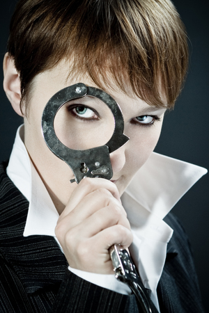 Woman wearing business suit suspiciously looks through handcuff as magnifying glass