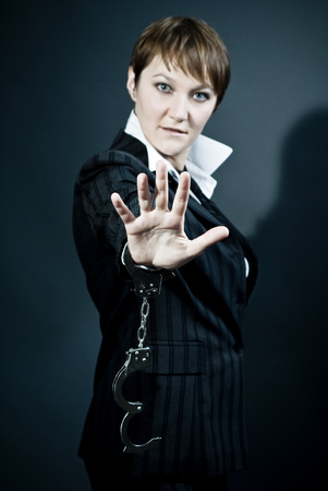 Woman wearing business suit gives stop signal by hand with handcuffs on Stock Photo