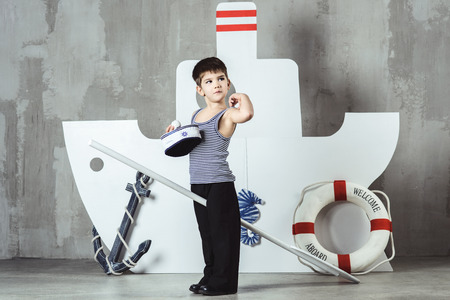 Cute cabin boy in striped t-shirt and sailor cap playing with paddle in front of stylized ship, studio shot