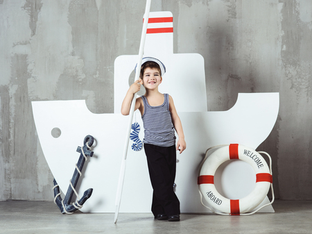 Cute smiling cabin boy in striped t-shirt and sailor cap playing with paddle in front of stylized ship, studio shot