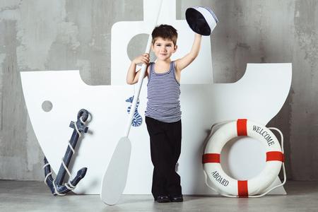 Cabin boy in striped t-shirt waving sailor cap in front of stylized ship, studio shot Stock Photo