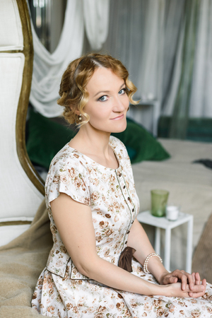 Portrait of a beautiful woman in a vintage dress in a light green pastel interior