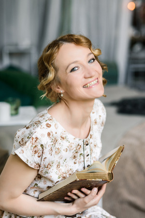 Portrait of a beautiful woman in a vintage dress with an old book in her hands