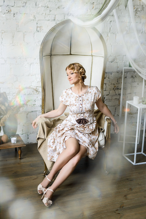 Portrait of a beautiful woman in vintage dress with her knees not covered