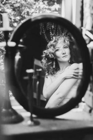 Reflection of beautiful woman admiring herself in the mirror, black and white shot