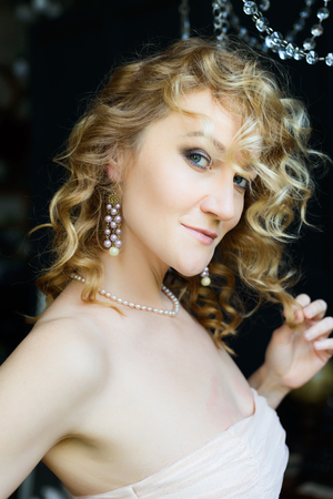 glamorous portrait of a beautiful blonde girl with curly hair