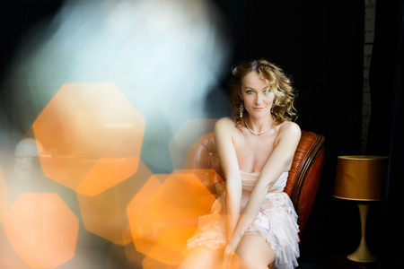 sensual portrait of a beautiful blonde girl with curly hair, light flares, glares, bokeh, yellow and orange color scheme