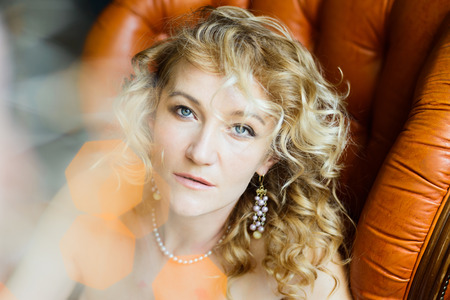 portrait of blonde woman with curly hair, light flares, glares, bokeh, yellow and orange color scheme
