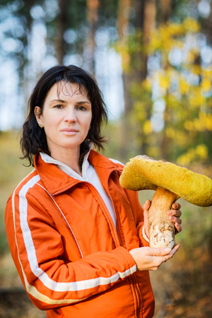 Portrait of an adult woman with a huge mushroom Boletus edulis in the forest on a sunny autumn day 写真素材