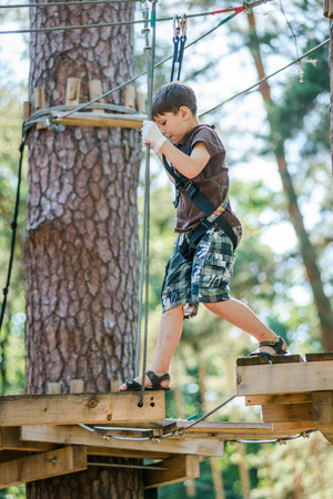 Boy passing cable route in extreme adventure rope park on sunny summer day Stock Photo