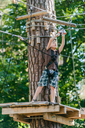 Boy passing cable route in extreme adventure rope park on sunny summer day Reklamní fotografie
