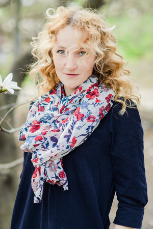 Spring portrait of blonde woman with curly hair, flower scarf