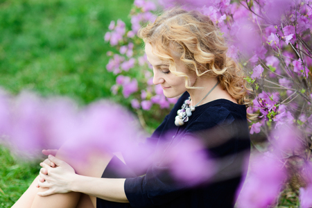 Spring portrait of thoughtful blonde woman with curly hair, violet flowers background