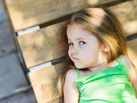 Cute little curly hair blonde girl lying on wooden bench looking at camera with scepticism
