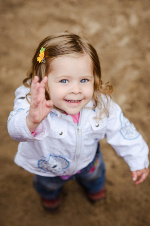 Cute girl waving and smiling at camera, shot from above
