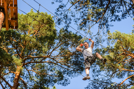 Man passing cable route in etreme adventure rope park on sunny summer day Stock Photo