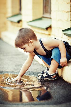 Cute little boy washing hands in puddle Foto de archivo - 114694604
