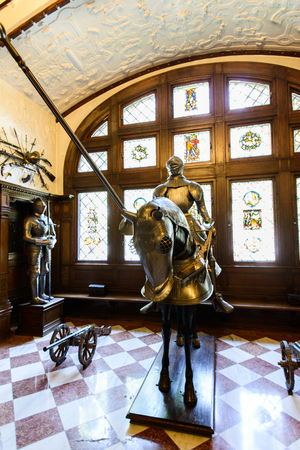 SINAIA, ROMANIA - AUGUST 20, 2014: The interior of beautiful Neo-Renaissance Peles palace castle in Carpathian mountains, built between 1873 and 1914 for King Carol I. The Armory hall or The Arsenal. Full knight and horse armour