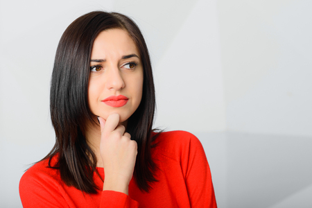 Portrait of beautiful brunette thoughtful young worried woman wearing red