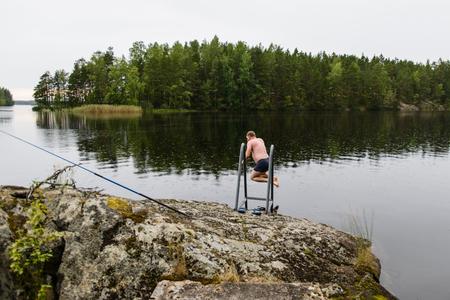 Uomo che salta nell'acqua del lago dopo aver fatto una sauna finlandese Archivio Fotografico