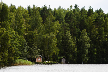 Far away summer view on finnish sauna buildings at forest near lake