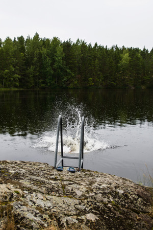Splash of water near ladder after man taking finnish sauna