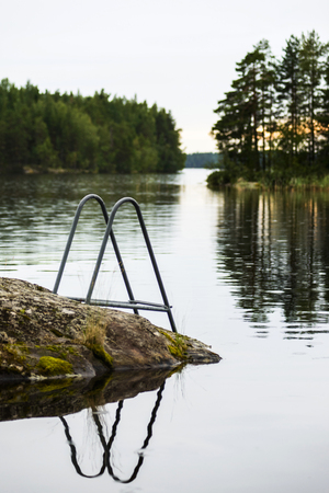 Ladder to lake near sauna cabin in Finland landscape Stock Photo