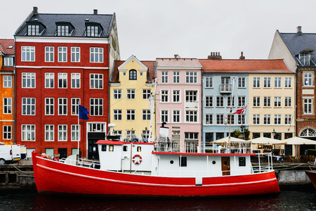 Beautiful red and white boat in front of colourful old dannish houses at Nyhavn harbour canal, Copenhagen, on spring gloomy day Stock Photo