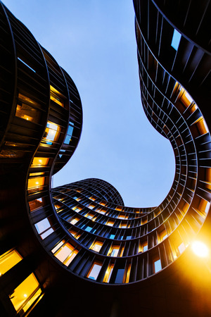 A view towards the dark evening sky from inner yard shapes of round Axel Towers, example of new Danish architecture in the centre of Copenhagen, comprising space for living, work, recreation, entertainment Redactioneel