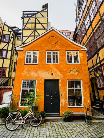 Cute hipster rose bike with basket at doors of colorful orange old town danish house