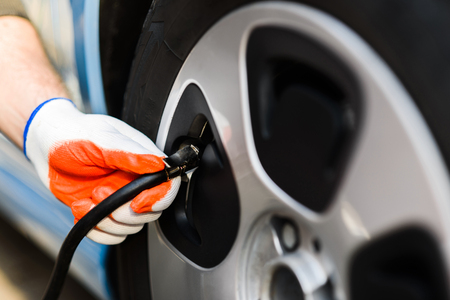 driver checking air pressure in the tires close up Stock Photo