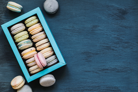 pastel macaroons box on dark wooden background, copy space