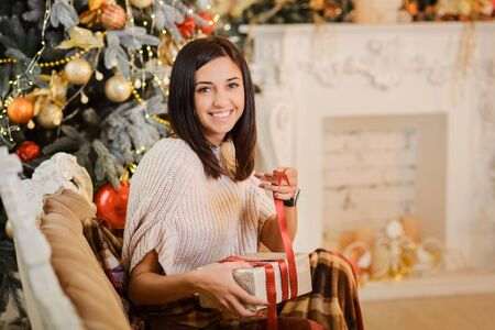 girl wrapping christmas gifts with ribbon at decorated home