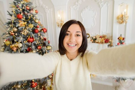 girl taking cristmas selfie with mobile phone