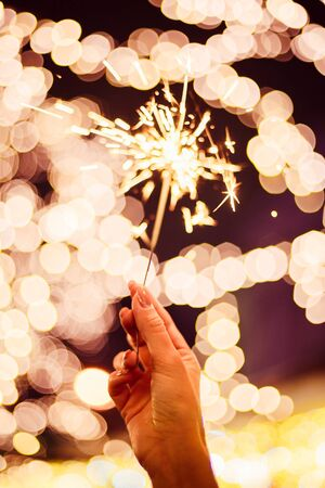 Bright new year celebration sparkler in a girls hand on yellow red bokeh background