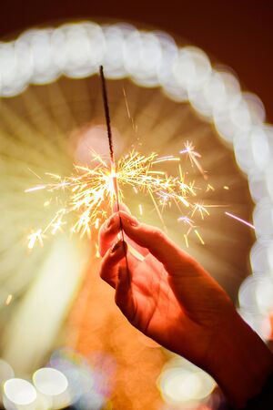 Bright new year celebration sparkler in a girls hand on yellow red ferris wheel bokeh background