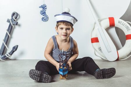 Cabin boy in sailor cap playing with model of ship Stock Photo