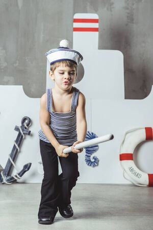 Cabin boy playing with paddle in front of stylized ship