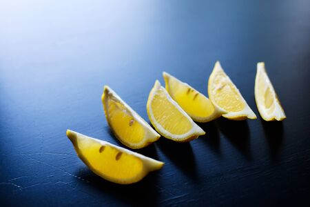 fresh yellow sliced lemon on dark blue table background, copyspace